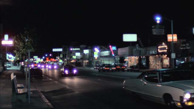traffic traveling in both directions on well lit street with businesses and buildings in bg. camera pans l-r on dark car as it turns left through intersection. - anno 1975 video stock e b–roll