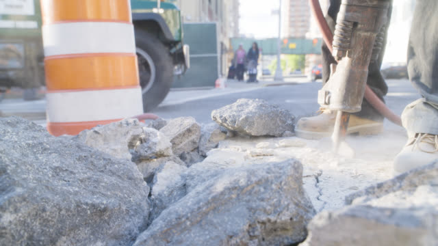 close angel of construction workers using jackhammer on concrete. construction worker. wheelbarrows, shovels, and boots visible. - 2014 stock videos & royalty-free footage