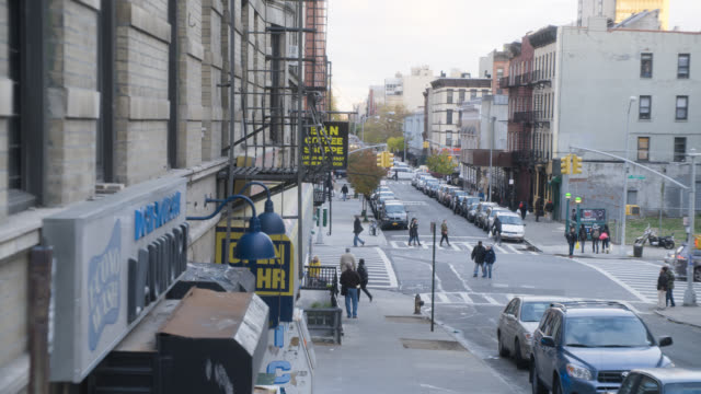 wide angle of city streets. brick apartment buildings, laundromats, and café visible. pedestrians and cars. - launderette stock videos & royalty-free footage