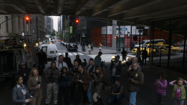 medium angle of photographers taking pictures. could be press junket. reporters and microphones. city street in bg. - 2014 stock videos & royalty-free footage