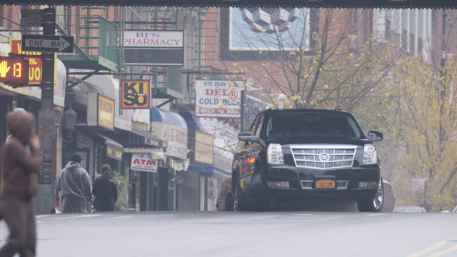 wide angle of black suv driving on city street. suv passes under bridge or overpass and parks. pedestrians visible. taxis visible. - sports utility vehicle stock videos & royalty-free footage