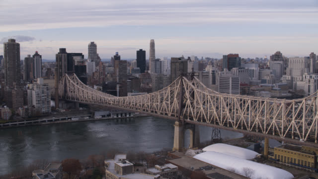 wide angle of queensboro bridge and city skyline. east river visible. high rises office buildings and apartment buildings. - queensboro bridge stock videos & royalty-free footage