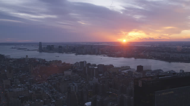 aerial of new york city skyline at sunset. statue of liberty and new york harbor visible. rivers visible. - porto di new york video stock e b–roll