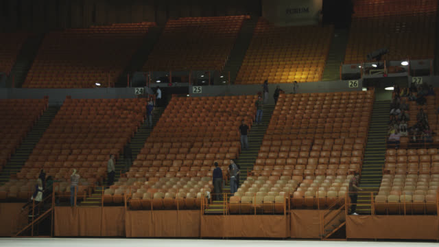 wide angle of stadium, auditorium, or concert venue. the forum. people visible on stairs while others sit. - auditorium stock videos & royalty-free footage