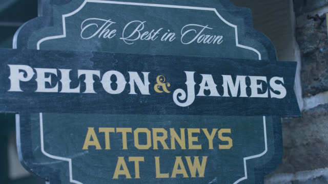 """close angle of sign for law office. sign reads """"the best in town. pelton and james. attorneys at law."""" - 1890~1899年点の映像素材/bロール"""