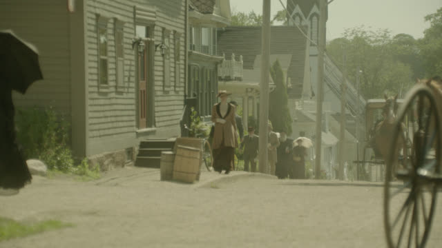 wide angle of people walking on sidewalk of residental area. houses line street. women carry parasols. church and horse drawn carriages visible in bg. barrels and bicycle in fg. - 19th century stock videos & royalty-free footage