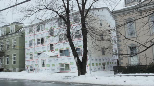 stockvideo's en b-roll-footage met wide angle of residential area. houses or multi-story townhouses visible. house in fg under construction. treees and snow visbile. - stadswoning