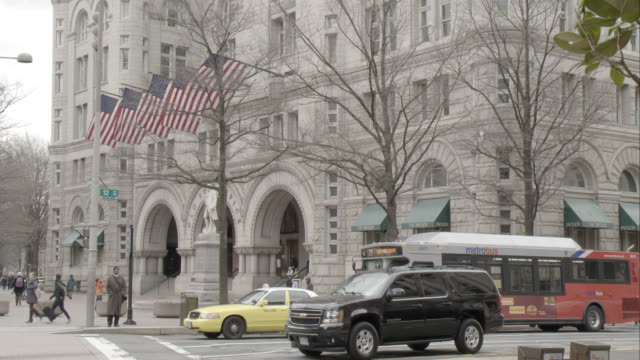 medium angle of cars driving on city streets. pedestrians visible. american flags visible on old post office pavillion in bg. could be hotel or restaurant. - 2013 stock videos & royalty-free footage