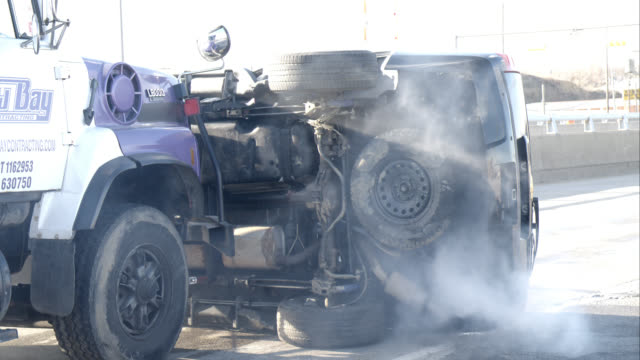 medium angle of work truck or dump truck pushing overturned black suv on freeway or highway. men in hazmat suits dump chemicals from back of dump truck. could be terrorists. - heavy goods vehicle stock videos & royalty-free footage