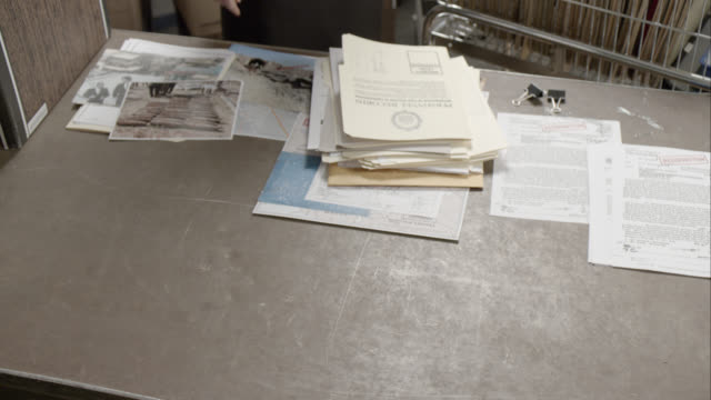 close angle of fbi files and folders on desk. could be office. maps, pictures, and photographs visible. people move folders around. - 2013 stock videos & royalty-free footage