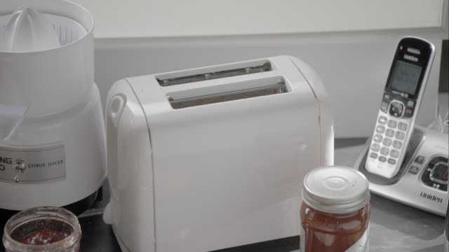 close angle of hand pushing button on toaster in kitchen. telephone, juicer, and jars jam visible. - toaster appliance stock videos & royalty-free footage