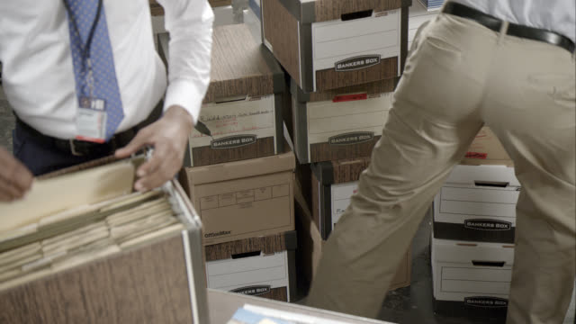 close angle of two fbi agents sifting or searching through files boxes. - file stock videos & royalty-free footage