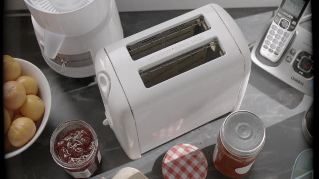 high angle down of hand pushing button on toaster in kitchen. telephone, juicer, and jars jam visible. - toaster appliance stock videos & royalty-free footage