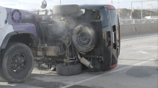 medium angle of work truck or dump truck next to overturned black suv. could be accident or collison. car stunts. - traffic accident stock videos & royalty-free footage