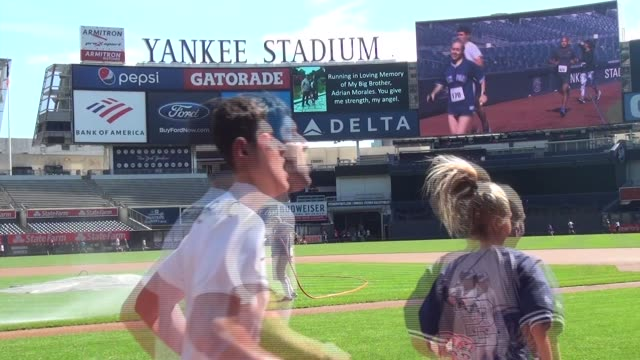 runners in yankee stadium 5k run on warning track around infield and outfield worker waters infield grass video screen shows runners - salmini stock videos & royalty-free footage