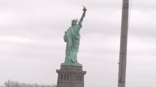 zoom out from statue of liberty to reveal a flag field at halfmast - salmini stock videos & royalty-free footage