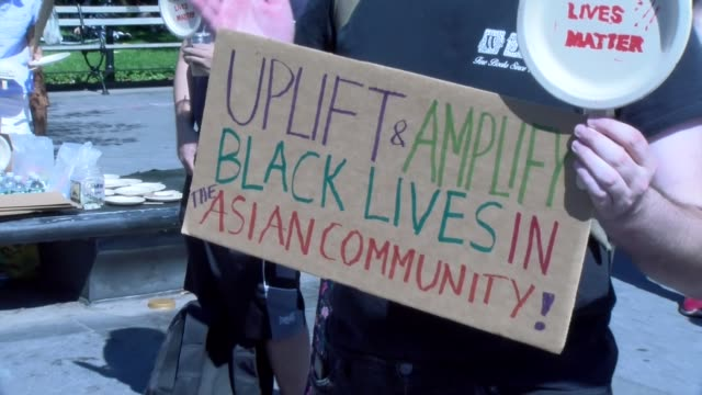 peaceful protestor holds sign uplift and amplify black lives in the asian community - salmini stock videos & royalty-free footage
