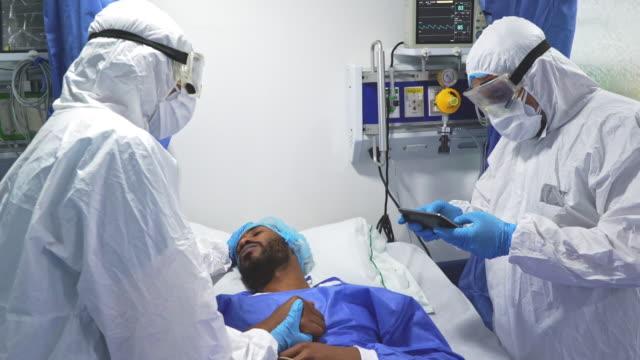 2人の医師がケアルームであなたの患者に話しかける。これは cuvid 19 の間に起こります。 - レスピレーターマスク点の映像素材/bロール