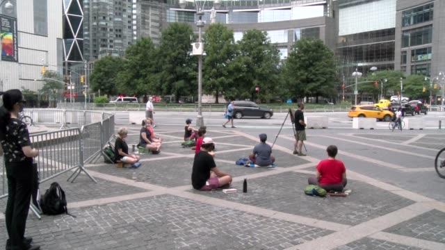 meditation for racial justice in columbus circle pan down from time warner center - salmini stock videos & royalty-free footage