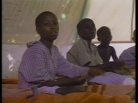 at red cross hospital in kigali; two children smile as they stand in doorway of large tent. one boy sits up on cot on floor of tent as boy beside him... - フツ族点の映像素材/bロール