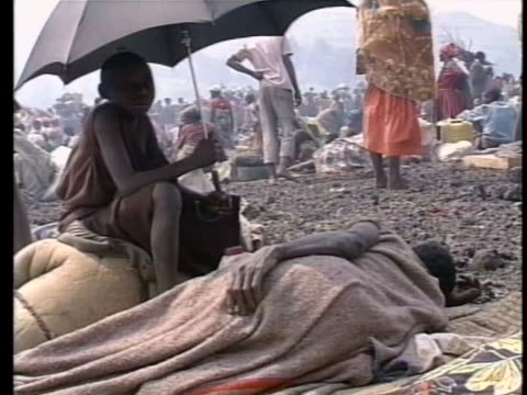 people inside clinic tent hold up iv bags. closeup of face of cholera victim lying in tent seen. boy sits with umbrella next to person lying on... - フツ族点の映像素材/bロール