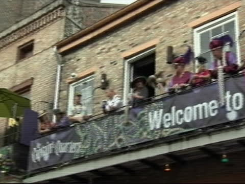 pan of people on balcony on bourbon street in costumes and with beads during mardi gras there's a sign that says welcome to mardi gras 2012 - gras stock videos & royalty-free footage