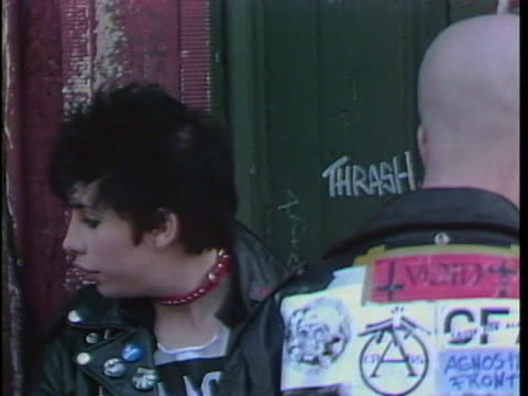 girl with shaved head& maltese cross earring stands on sidewalk. youths with mohegan haircuts; leather jackets;& torn blue jeans stand outside punk... - punk music stock videos & royalty-free footage