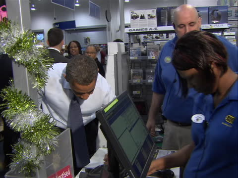president obama in best buy at register paying for gifts for daughters sasha and malia with credit card he swipes signs and takes bag from cashier... - shirt and tie stock videos & royalty-free footage