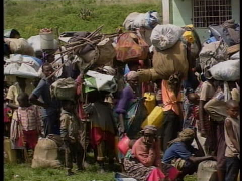 in rwanda refugees at border seen. belongings are searched. crowd of refugees in field - フツ族点の映像素材/bロール