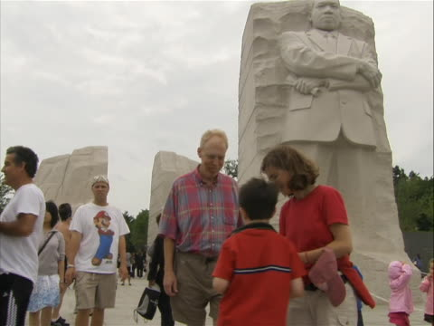 boy takes picture of a couple standing in front of the 'stone of hope' from the mlk jr. memorial. - engraved image stock videos & royalty-free footage