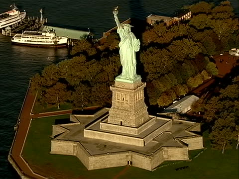 vidéos et rushes de aerial beauty shot of statue of liberty in the fall with park with trees in background great stock shot - war in afghanistan: 2001 present