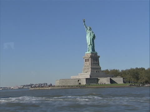 ws of statue of liberty from moving boat/ferry with statue cruises boat going by in the shot you can see the waves the boat is making - war in afghanistan: 2001 present stock videos & royalty-free footage