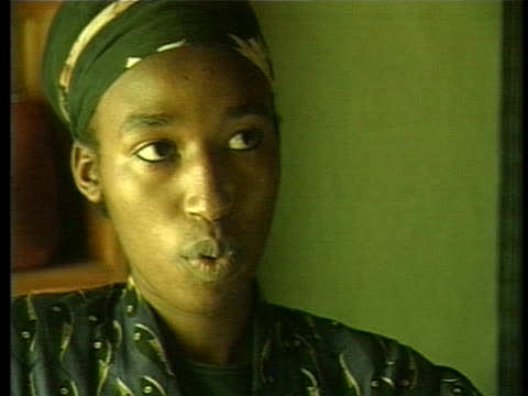 small room to show three young tutsi women he is hiding for their safety. closeup of their faces seen. - フツ族点の映像素材/bロール