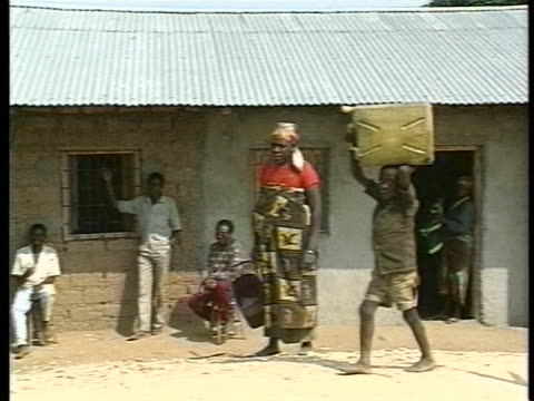boy carries large plastic container on his head while walking past villagers leaning against building. - フツ族点の映像素材/bロール
