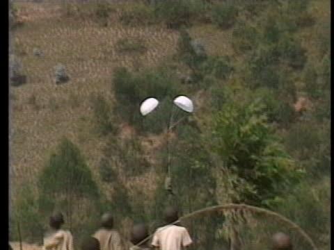 french army plane dropping bundles of food& medicine via parachute into valley. refugee children run down hillside to retrieve bundle. in zaire - フツ族点の映像素材/bロール