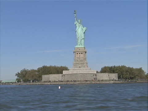 ws of statue of liberty from moving boat/ferry with slight zoom in you can see the waves the boat is making - war in afghanistan: 2001 present stock videos & royalty-free footage