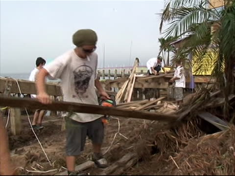 people cleaning up sawing debris in north carolina in aftermath of hurricane irene zoom in and out to of saw - north carolina us state stock videos & royalty-free footage