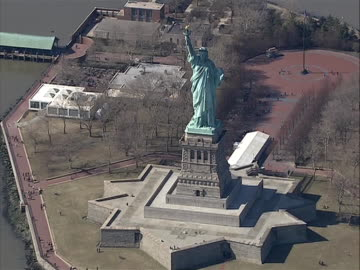 vídeos y material grabado en eventos de stock de great stock shot zoom out from of statue of liberty to aerial of liberty island with park in background - war in afghanistan: 2001 present