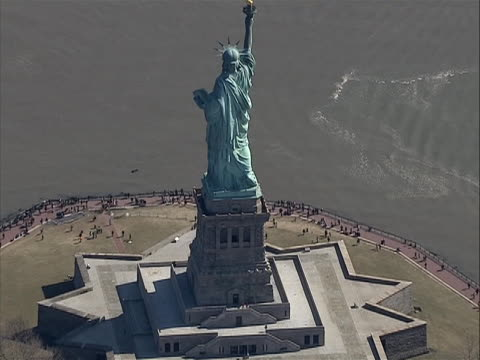 vidéos et rushes de zoom out from ws of tourist at base on liberty island to overhead ws shot of statue of liberty from behind great stock shot - war in afghanistan: 2001 present