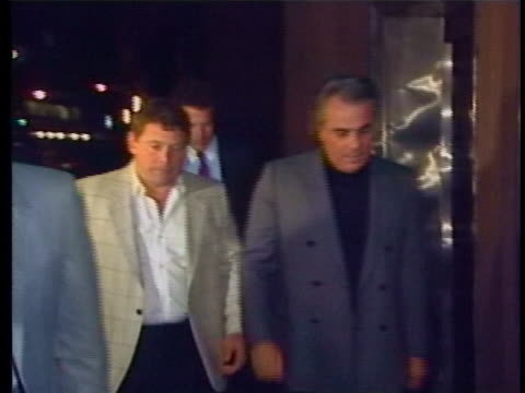 close up of gotti walking with men at night including sammy the bull gravano who puts up hand to cover camera - organised crime stock videos & royalty-free footage