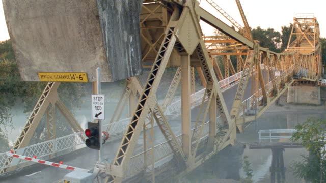 sunset - metal draw bridge starting to lift - drawbridge stock videos & royalty-free footage