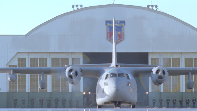 dx - air force c-123 transport plane lt. to rt. + stop - hangar in b.g. - g force stock videos & royalty-free footage