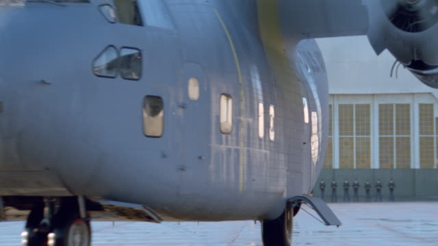 dx - airforce c-123 transport plane taxis circles around runway - fort         maccallum hangar with soldiers lined up in b.g. - g force stock videos & royalty-free footage