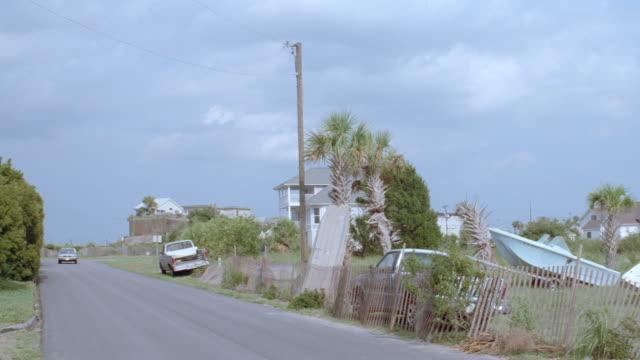 dx - rd past rundown marina - 1970s blue ford sedan by - pan to lighthouse - sedan stock videos & royalty-free footage