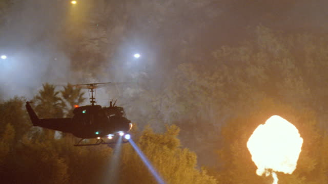 nx - ground to air - huey military helicopter circling active training         battlefield w/explosions + smoke - military helicopter stock videos & royalty-free footage