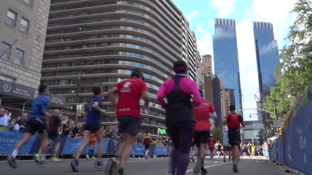 vidéos et rushes de spectators cheer as runners get close to finish line - time warner towers up ahead - salmini
