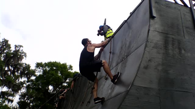 entrants pull themselves up steep ramp using ropes - salmini stock videos & royalty-free footage