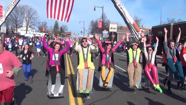 thousands of runners in costume head down main street after their 4 mile run - salmini stock videos & royalty-free footage