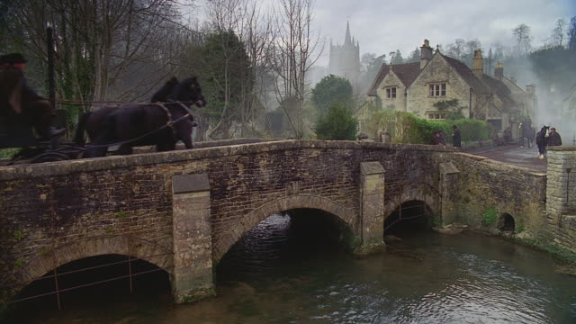 stockvideo's en b-roll-footage met old english village; turn of the century period traffic (actually castle combe, wilshire, uk) - paardenkar