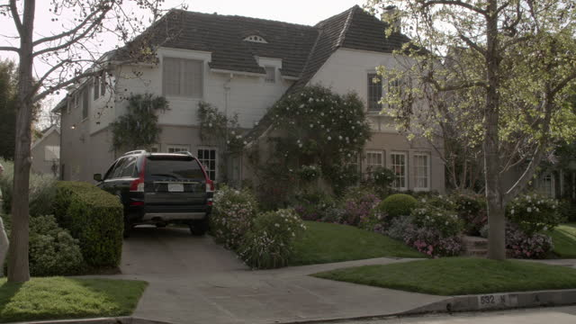 vidéos et rushes de pan right to left of upper class house or mansion in residential area or neighborhood. volvo suv parked in driveway. bushes, shrubs, trees, and flowers visible in front yard. pedestrians visble on sidewalks and cars drive on street. - quartier résidentiel